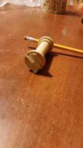 Side view of broken toothpick, stuck through the other end of the rubber band and held with masking tape